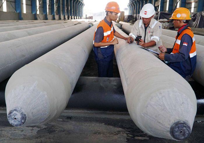 Tiga orang pekerja mengecek produk precast berupa Spun Pile atau tiang pancang beton di PT Waskita Beton Precast Plant Prambon, Sidoarjo, Jawa Timur. Istimewa/Waskita.