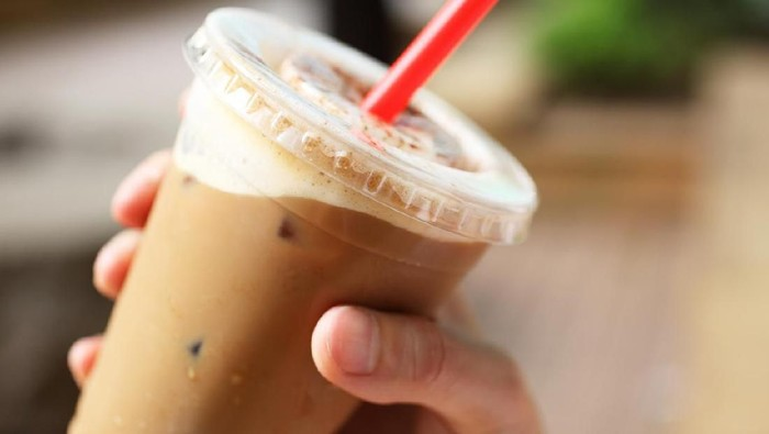 A cup of iced coffee in hand outdoors.