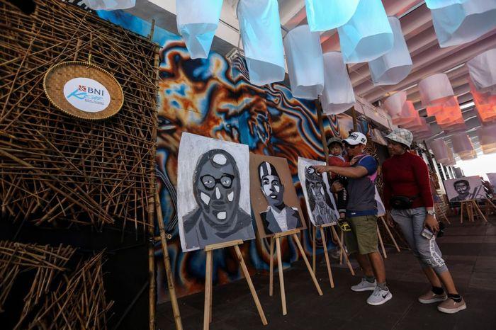 Pengunjung sedang melihat hasil karya seni dari barang bekas yang dipamerkan pada aksi BNI KEJAR atau Kenali Sejarah Raihlah Mimpimu di Terowongan Dukuh Atas, Jakarta, Minggu (24 November 2019).
