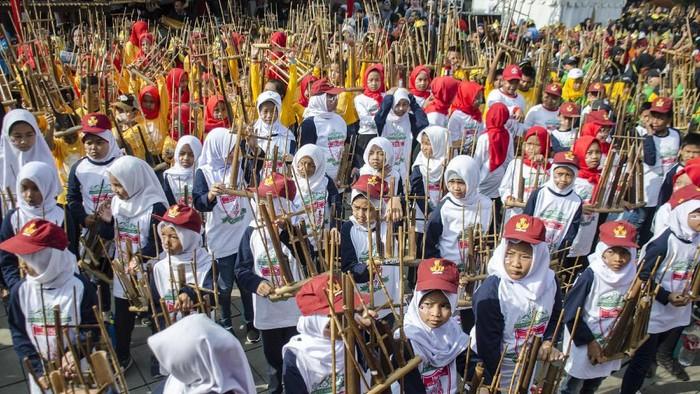 Sejumlah pelajar SD memainkan alat musik angklung secara bersama pada acara Angklungs Day 2019 di Gedung Sate, Bandung, Jawa Barat, Minggu (24/11/2019). Angklungs Day 2019 yang bertemakan Feel The Worlds Sensation tersebut guna memperingati alat musik angklung sebagai warisan budaya dunia tak benda oleh UNESCO serta untuk menggali nilai tradisional dalam berkesenian dan berkebudayaan bagi generasi muda. ANTARA FOTO/Novrian Arbi/aww.