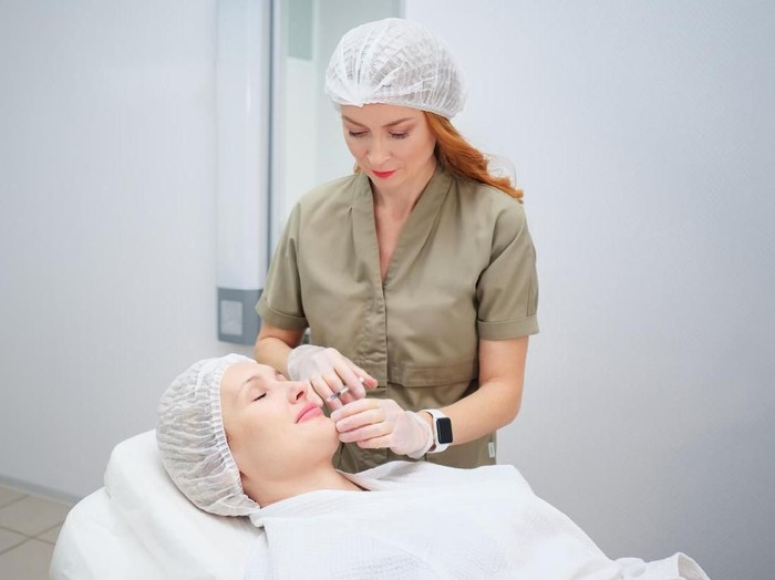 beauty doctor carries out cosmetological procedure injecting collagen filler to increase lips size