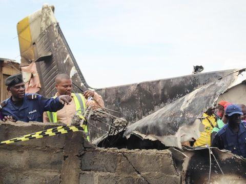Petugas penyelamat dan warga setempat mengamati lokasi jatuhnya pesawat