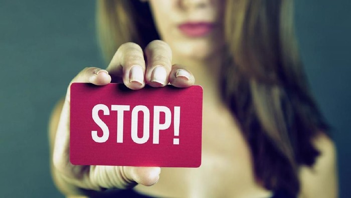 Young woman holding stop card on dark background