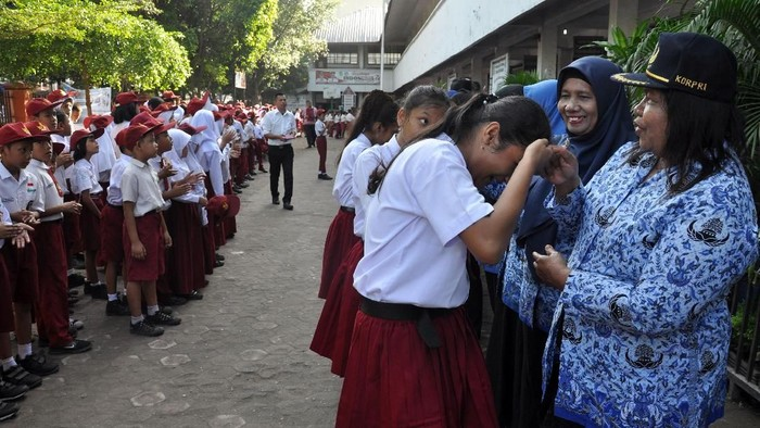 Sejumlah siswa menyalami guru mereka seusai mengikuti upacara di Sekolah Dasar Negeri 060813 Medan, Sumatera Utara, Senin (25/11/2019). Menyalami guru oleh para siswa tersebut dalam rangka memperingati Hari Guru yang serentak dilaksanakan di seluruh Indonesia. ANTARA FOTO/Septianda Perdana/foc.