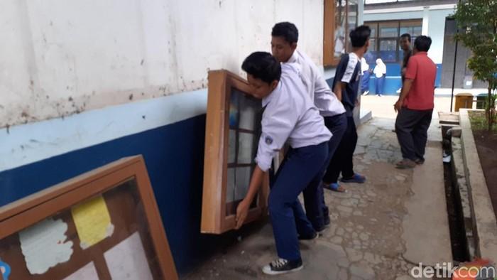 Sejumlah siswa SMP di Kabupaten Bandung Barat ikut membereskan ruang kelas yang akan dibongkar karena terkena proyek KCIC. (Yudha Maulana/detikcom)