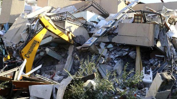 Sebuah buldoser dikerahkan untuk menyisir reruntuhan bangunan yang ambruk akibat gempa