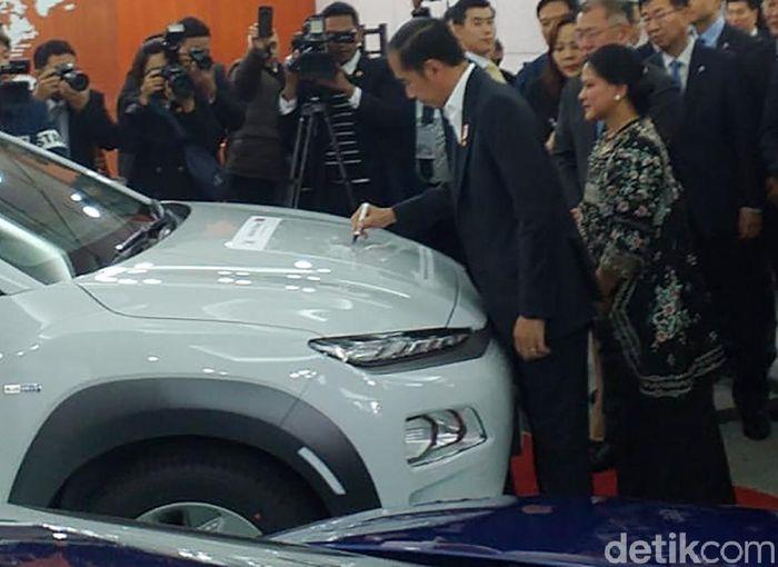 Presiden Joko Widodo bersama Ibu negara Iriana Joko Widodo mengunjungi pabrik Hyundai di Ulsan, Korea Selatan. Setibanya di pabrik Hyundai, Jokowi langsung menandatangani mobil putih bernama Kona Electric ini.
