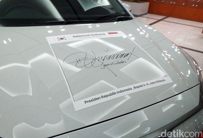 Penandatanganan dilakukan Jokowi di atas kap mobil.