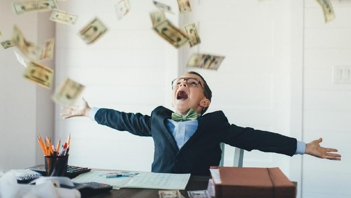 A young entrepreneur boy businessman is dressed in business attire and is working hard on his business while earnings in US currency are raining from the sky. He loves earning money from his new business and saving his money in the bank.
