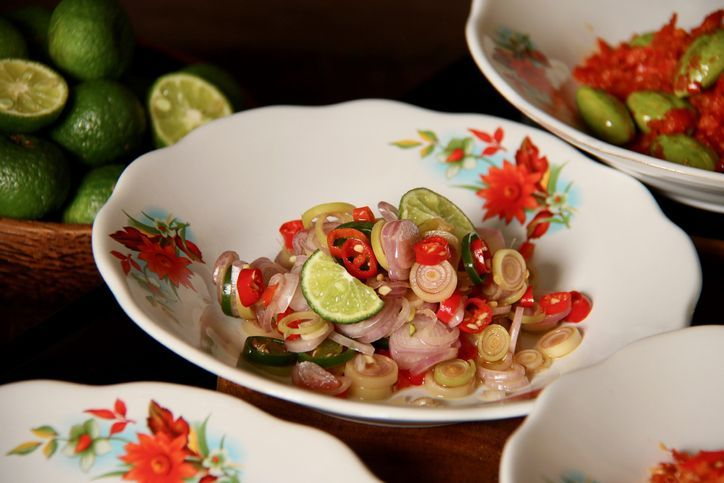 Sambal Matah, a popular salsa condiment of chopped chili peppers with lemon grass and shallots from Bali. The condiment is plated on old-fashioned crockery with red flowers paintings. It is served together with other popular spicy condiments from several other regions in Indonesia.