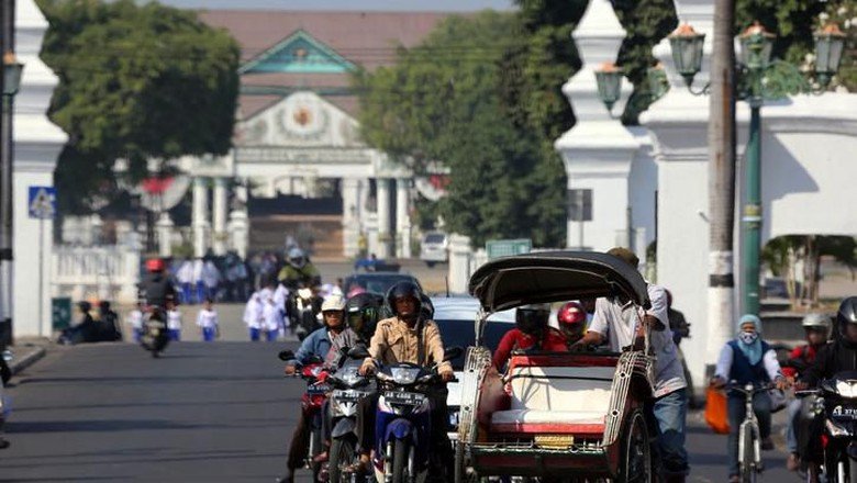 Yogyakarta, Indonesia - August 13, 2014: Varioius forms of transportation all together at a traffic stop in central Yogyakarta.