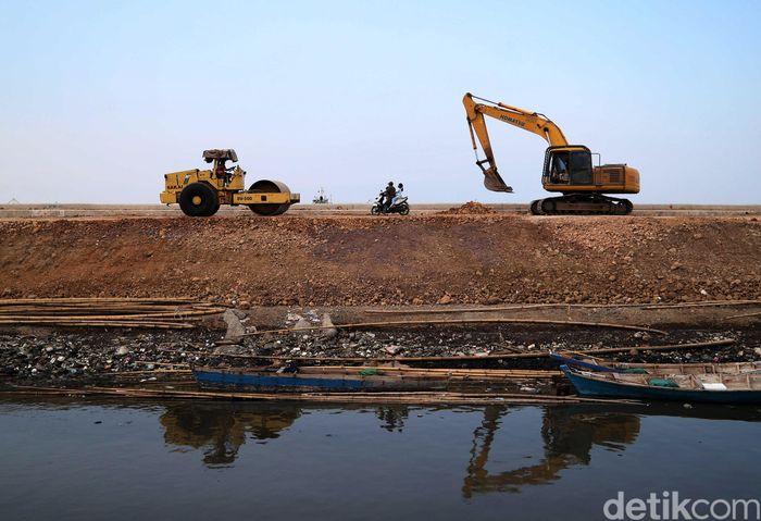 Alat berat meratakan tanah yang akan dibangun jalan di pinggir tanggul laut Cilincing, Kamis (28/11/2019).