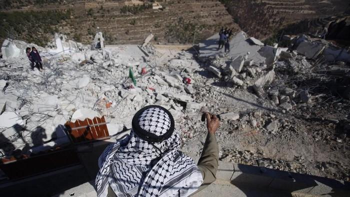Warga Palestina memandangi rumah-rumah yang dihancurkan militer Israel di Tepi Barat (AP Photo/Majdi Mohammed)