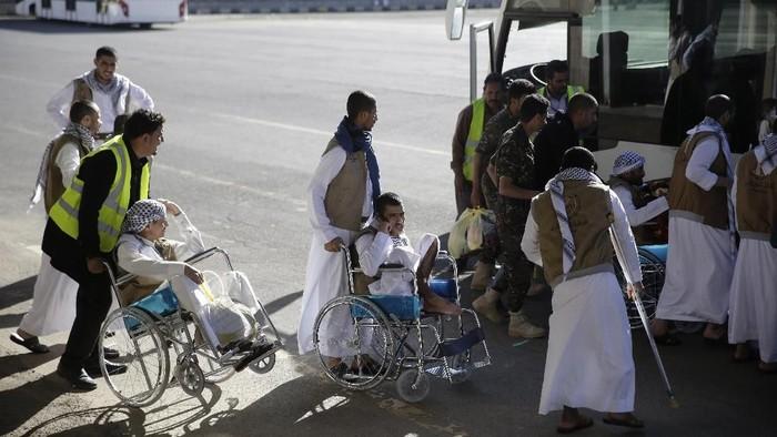 Tahanan Houthi berkumpul ke dalam bus usai mendarat di bandara Sanaa, Yaman (AP Photo/Hani Mohammed)