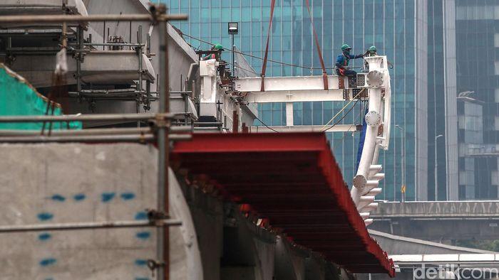 Para pekerja menyelesaikan konstruksi stasiun LRT di kawasan Rasuna, Said, Jakarta, Jumat (29/11/2019).