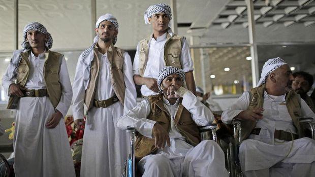 Tahanan Houthi yang baru dibebaskan menunggu keluarga mereka tiba di bandara Sanaa, Yaman