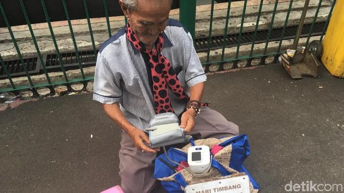 Kakek penjual jasa timbang badan dan ukur tensi di Stasiun Bogor (Foto: Nafila Sri Sagita K)