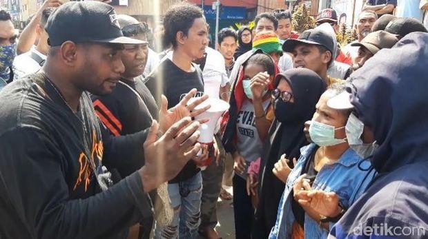 Pendemo (Pria bertopi hitam) adu mulut dengan mahasiswa yang menolak aksi Pro-Papua Merdeka.