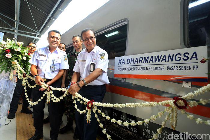 Direktur Utama PT KAI Edi Sukmoro didampingi Executive Vice President Daop I Jakarta Dadan Rudiansyah memotong rangkaian bunga sebagai tanda diresmikannya kereta api Dharmawangsa, Senin (2/12/2019).