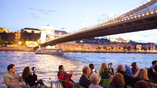 People sitting in a cruise boat on the Danube river and passing under Chain Bridge at summer night