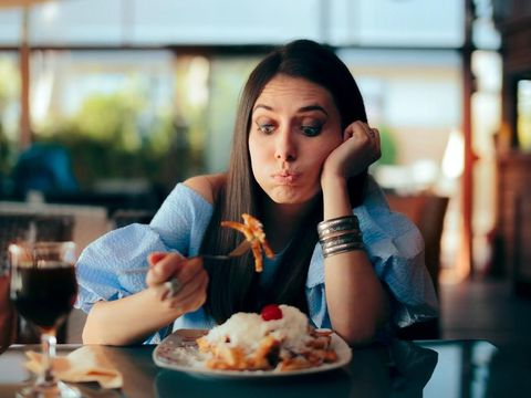Person experiencing overeating side effects at lunch