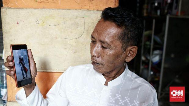 Budi Sulistyo (55), menunjukkan foto Luthfi Alfiandi yang tengah membawa bendera.