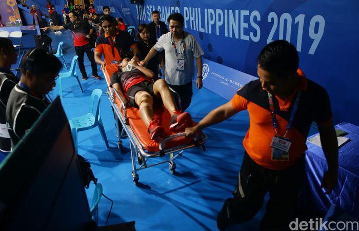 Gregoriaditandu keluar lapangan setelah kaki kanannya cedera saat melawanRatchanok Intanon diMuntinlupa Sports Complex, Selasa (3/12/2019).