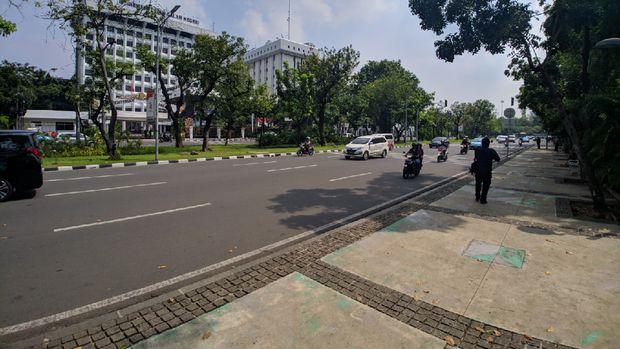 Lalu lintas di jalan ini nampak ramai dan lancar.