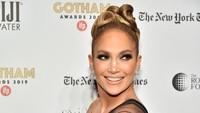 J-Lo tampak mengenakan gaun hitam menerawang dengan tambahan aksen bulu. (Theo Wargo/Getty Images for IFP)