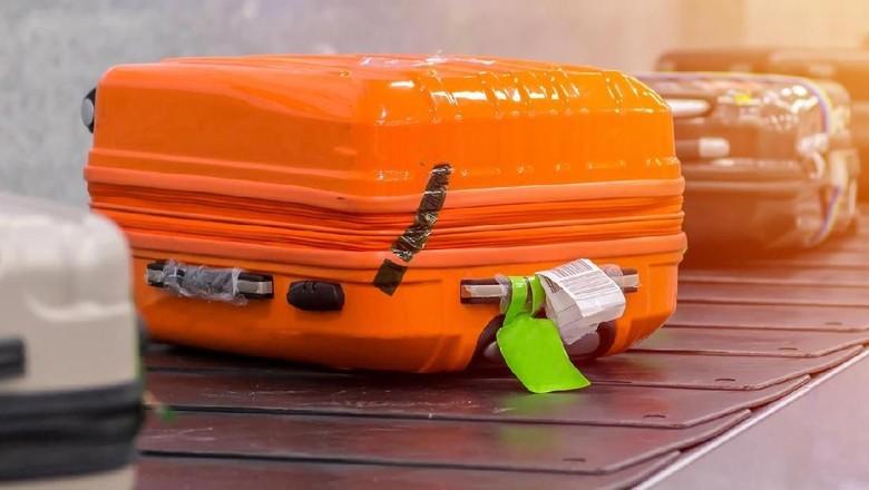 Ilustrasi koper, beserta label tag-nya, di atas ban berjalan alias conveyor belt bandara. (Foto: iStock)