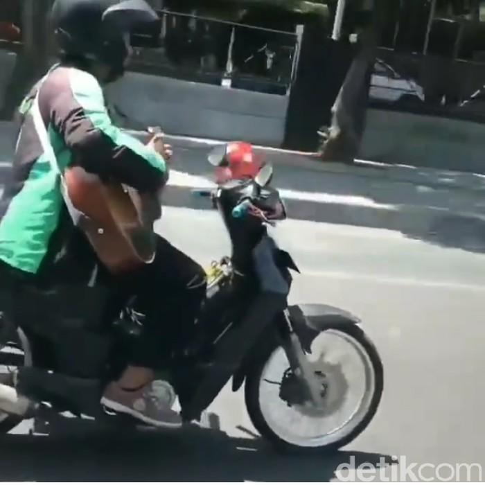 Saat pria mengendarai motor sambil main gitar/Foto: Tangkapan Layar