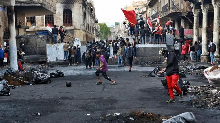 Demonstran antipemerintah di Irak berkumpul di dekat pembatas yang dipasang pasukan keamanan (AP Photo/Khalid Mohammed)