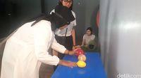 Simulasi sensorik dengan mengidentifikasi benda-benda lewat sentuhan.
