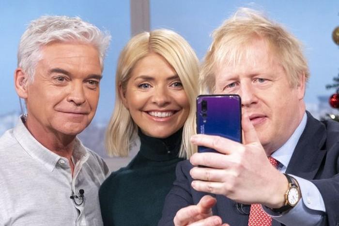 Boris Johnson pakai ponsel Huawei. Foto: Mirror