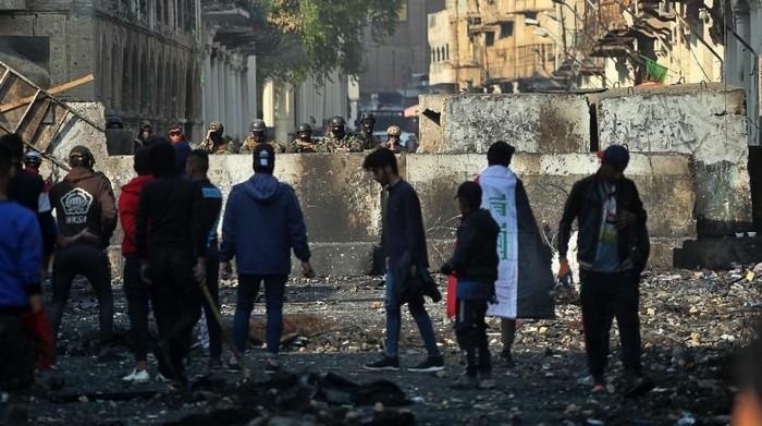 Demonstran antipemerintah di Baghdad saat berhadapan dengan pasukan keamanan Irak (AP Photo/Khalid Mohammed)