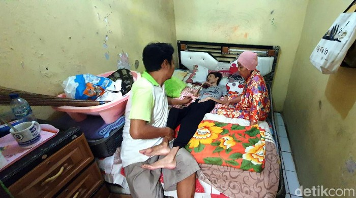 Purwanto setia merawat istrinya, Tati Sujiwati (37), yang terbaring di tempat tidur. (Foto: Syahdan Alamsyah/detikcom)