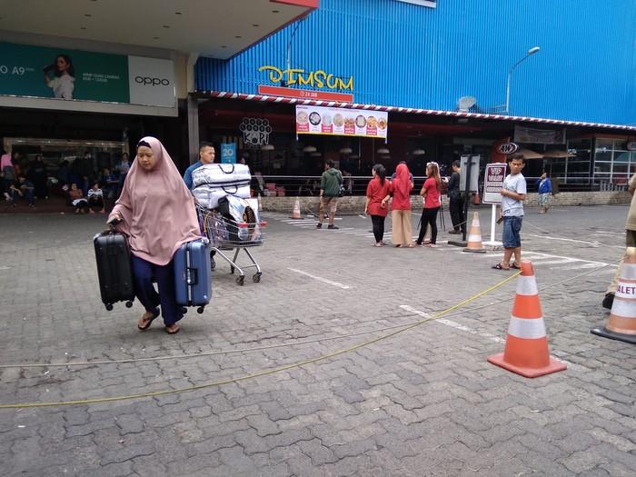 Pedagang di Mal Lokasari tampak mengangkut barang dagangan keluar dari dalam mal. (Kadek Melda/detikcom)