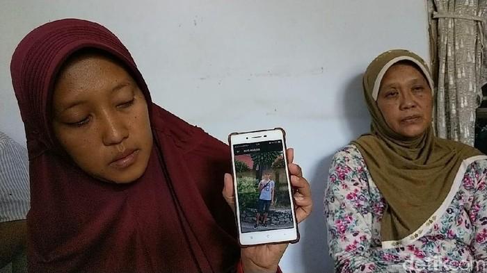 Kakak perempuan Ilyas menunjukkan foto adiknya (Foto: Adhar Muttaqin)