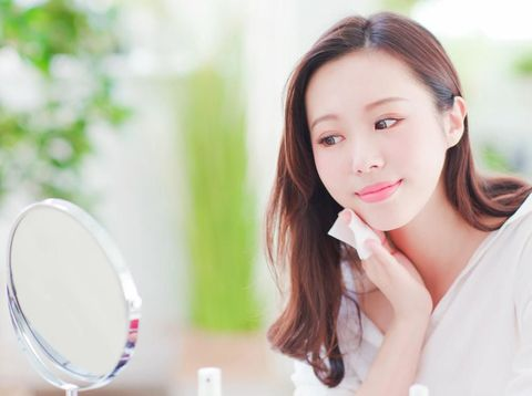 Smile asian woman remove makeup by Cleansing Cotton and look mirror at home