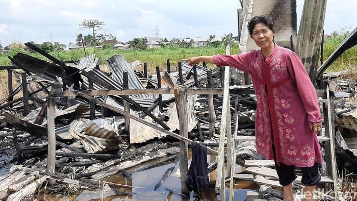 Nurmili menunjukkan rumah yang dibakar Vije. Foto: Raja Adil Siregar