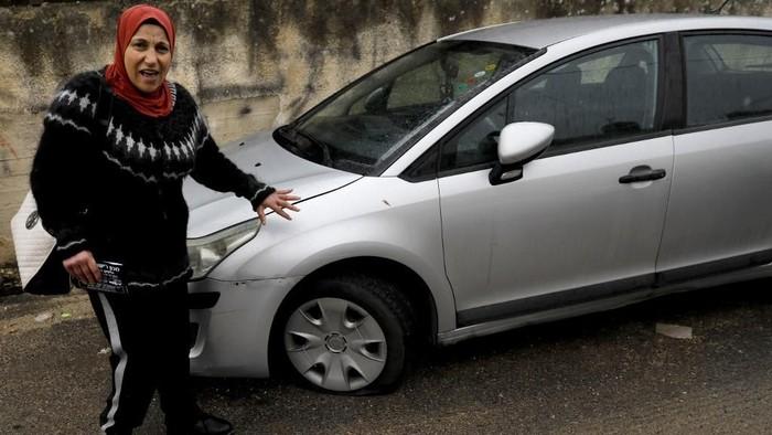Seorang wanita Palestina menunjukkan mobilnya yang dikempesi oleh pelaku vandalisme (AHMAD GHARABLI/AFP)