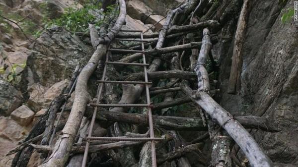 Warga setempat menyebut tangga menjalar yang terbuat dari kayu dan menempel pada tebing terjal itu, sebagai tangga langit. Untungnya, tidak setiap hari anak-anak sekolah itu memanjat tebing terjal (Foto: CNN)
