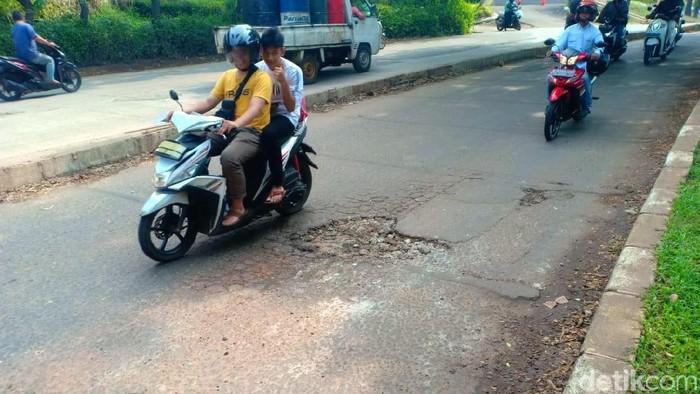 Jalan berlubang di GDC Depok, lokasi Ustaz Beben kecelakaan, ditambal pasir dan batu. (Faisal/detikcom)