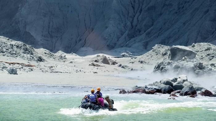 Petugas penyelamat meninggalkan White Island usai terjadi erupsi gunung api (Michael Schade via AP)