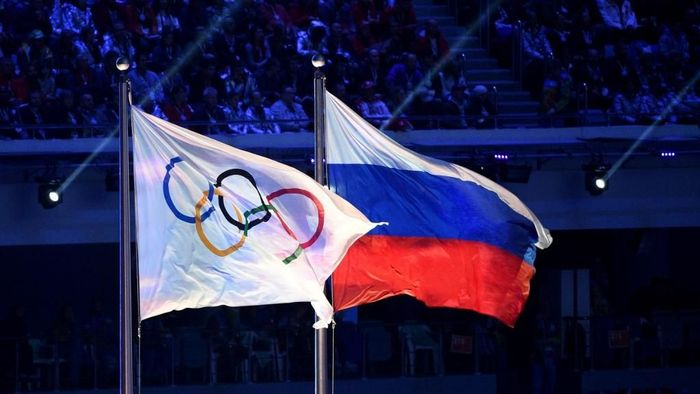 (FILES) This file photograph taken on February 23, 2014, shows the Olympic flag and the Russian flag flying during the Closing Ceremony of the Sochi Winter Olympics at the Fisht Olympic Stadium in Sochi. - The World Anti-Doping Agency (WADA) decided on December 9, 2019, to exclude Russia from the Olympic Games for four years, including Tokyo-2020 and Beijing-2022, to sanction the falsification of test data submitted to the agency, a WADA spokesman said after the Executive Committee meeting in Lausanne (Photo by Andrej ISAKOVIC / AFP)