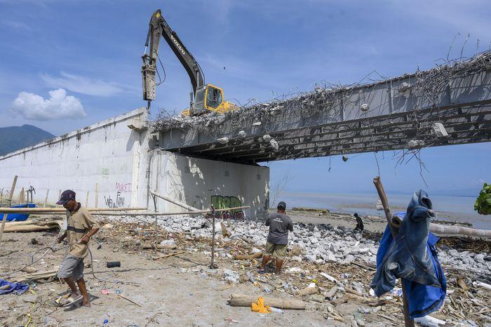 Sejulmlah pekerja mengumpulkan besi-besi rangka Jembatan Palu IV yang dirobohkan di Pantai Kampung Lere, Palu, Sulawesi Tengah, Rabu (11/12/2019).