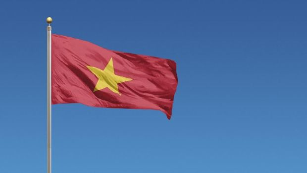 Flag of Vietnam in front of a clear blue sky