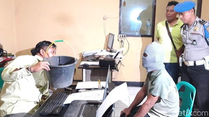 Tersangka dalam kasus sabung ayam di Kota Probolinggo (memakai topeng). (M Rofiq/detikcom)
