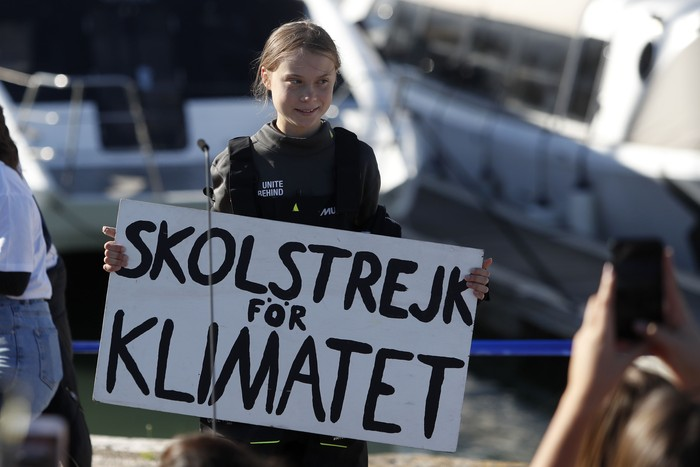 Climate activist Greta Thunberg holds a sign reading School strike for the climate after arriving in Lisbon, aboard the sailboat La Vagabonde, Tuesday, Dec 3, 2019. Thunberg has arrived by catamaran in the port of Lisbon after a three-week voyage across the Atlantic Ocean from the United States. The Swedish teen sailed to the Portuguese capital before heading to neighboring Spain to attend the U.N. Climate Change Conference taking place in Madrid. (AP Photo/Armando Franca)