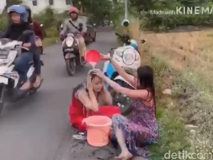 Dua wanita saat melanjutkan keramas di pinggir jalan/Foto: Tangkapan Layar
